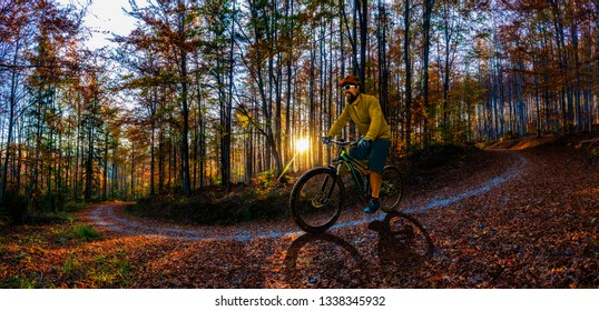 Single mountain bike rider on electric bike, e-mountainbike rides mountain trail. Man riding on bike in Beskidy mountains landscape. Cycling e-mtb enduro trail track. Outdoor sport activity.
