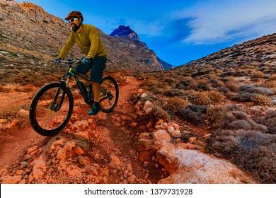 Single mountain bike rider on electric bike, e-mountainbike rides up mountain trail. Man riding on bike in Crete Greece landscape. Cycling e-mtb enduro trail track. Outdoor sport activity.