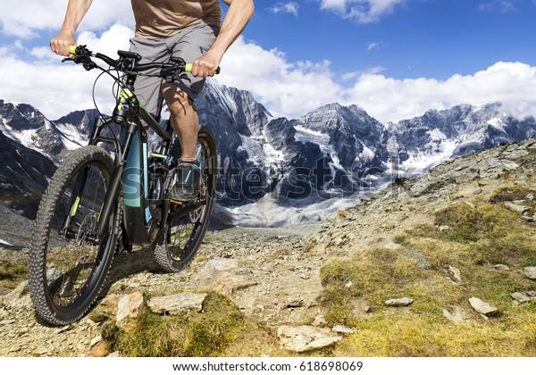Single mountain bike rider on ebike rides up a steep mountain trail.