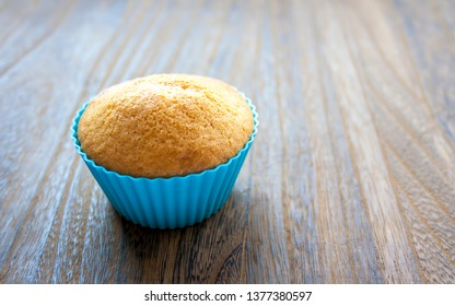 Single muffin on wooden table. Delicious cake for dessert.