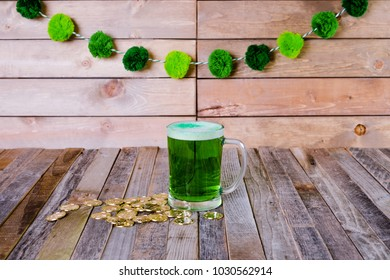 Single mug of green beer with golden coins on wooden background
