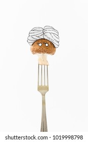Single mushroom on white background with turban sitting as a fakir on top of a silver fork representing indian food.