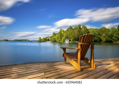 Single Muskoka chair sitting on a wood dock facing a lake. Across the calm water is a white cottage nestled among green trees. There is a boat dock on the water in front of the cottage.