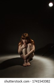A single naked girl is sitting with her arms around her knees on a black background