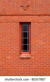 Single narrow leaded window in a red brick wall church