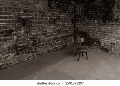 Single, old chair against old brick wall - black and white photo