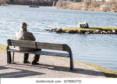 Single old man on sits on a bench