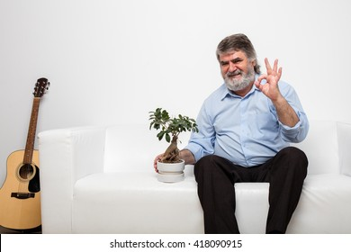 single old men sitting on white couch, tending a bonsai