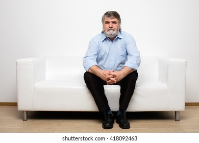 single old men sitting on white couch