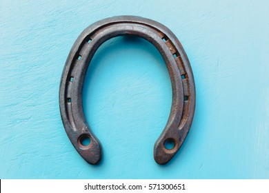 Single old rustic horse shoe on blue chalk painted blue wooden timber