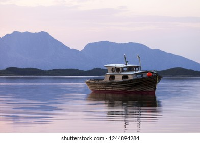 Single old wooden boat, reflection on sea surface, mountain Donna on background. Photographed in Helgeland, Norway.