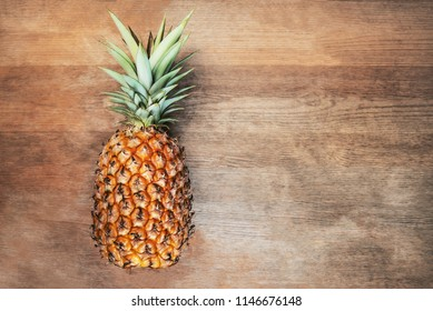 Single one full whole organic pineapple fruit on wooden background ripe fully grown mature, laid down on its side negative empty space for text