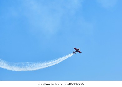 Single one sport plane of aerobatic team vapour trails in blue sky. Plane white vapour trails tracks background. Plane aerobatic maneuver stunt. Stunt planes aerobatic team vapor trails MAKS-2017