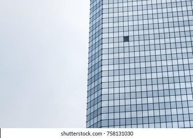 Single open window in glass window facade of corporate office skyscraper building, low angle view