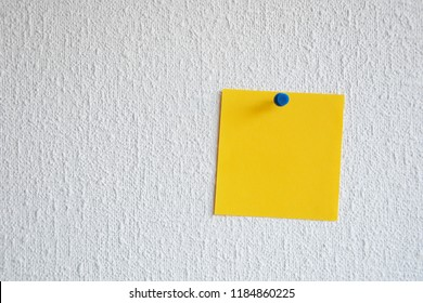 Single orange note pad reminder attached to the wall with pushpin. Empty memo note. Orange paper note tacked on a wall.
