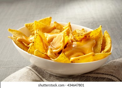 Single oval shaped white bowl of yellow tortilla chips topped with melted cheese placed on folded fabric napkin over tablecloth with copy space