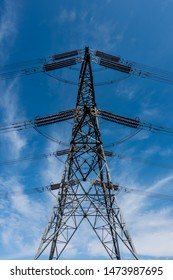 Single overhead line power pylon against a blue sky