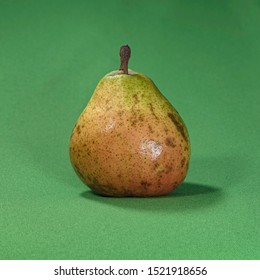 a single overripe comice pear sitting on bright green fabric showing details of color, texture and flaws