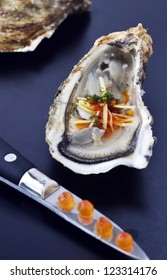 A single oyster with a chili and ginger garnish with an oyster shucker in the foreground with salmon roe balanced on the blade