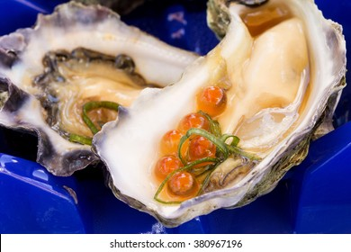 A single oyster live with garnish with an oyster shuck in the foreground with salmon roe.