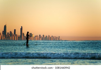 Single paddler against the Gold Coast skyline at sunset.