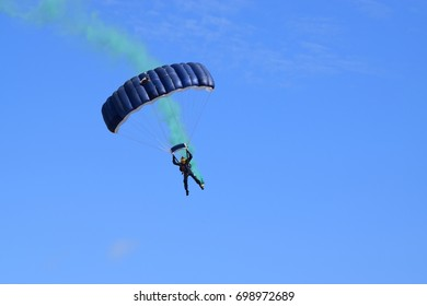 A single parachutist coming in to land - blue parachute