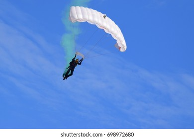 A single parachutist coming in to land - white parachute