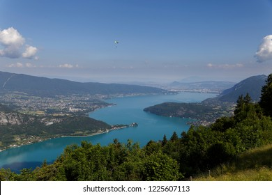 Single paraglider flying over the turquoise waters of  Lake Annecy  France