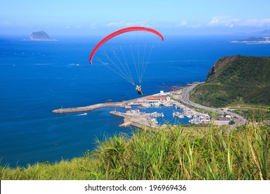 A single paraglider gliding in the air above the ocean.