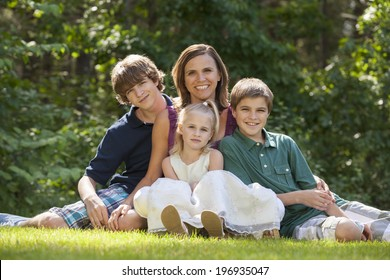Single parent family with three children sitting  on grass lawn and leaning on mother