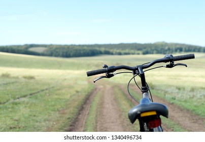 Single parked bike on a dirt road with a forest background and nobody in the travel scene