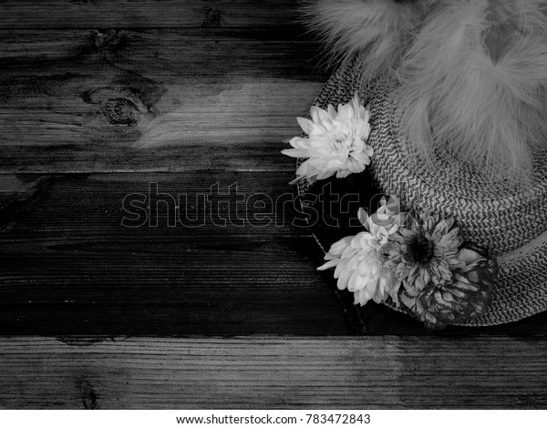 A Single Part Shown Easter Bonnet Hat Displaying a Brim of Flowers with a Feathered Top on a Black and White Wood Background