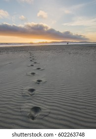 Single path of footsteps in sand on long beach in Tofino, British Columbia, Canada