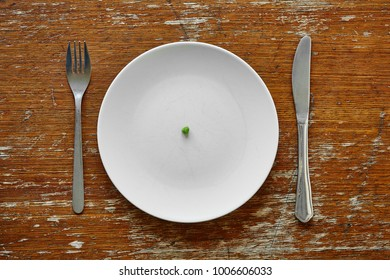 single pea on plate with knife and work metaphor for malnutrition