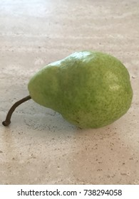 A single pear on a counter.