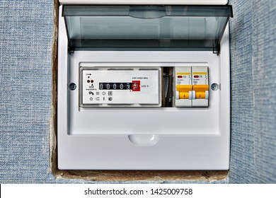 Single phase home electronic energy meter inside distribution board with electrical circuit breakers. Electricity meter located in electric meter box with electrical breaker fuse.