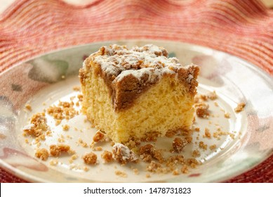 Single piece of coffee crumb cake served on a plate on a colorful pink and red placement.