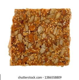 Single piece of honey nut crunch candy with sunflower seeds, almonds and sesame seeds isolated on a white background.