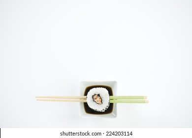 Single piece of maki sushi resting on chopsticks over dish of soy sauce, overhead view