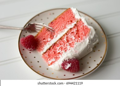 Single piece of pink raspberry cake on a small plate.