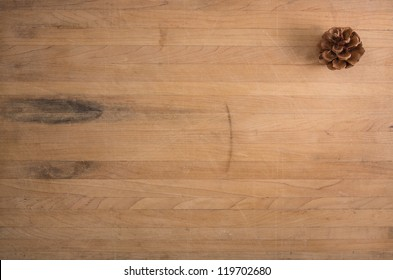 A single pine cone sits on a worn butcher block counter