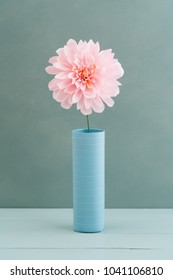 Single pink crepe paper dahlia in a vase on turquoise wooden background