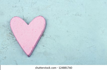 Single pink heart on light blue wooden table - shabby chic Valentine's day background