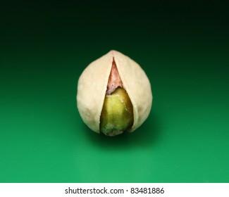 Single pistachio nut on a green background