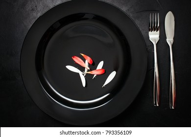 Single plate with fork and knife on black background. Dinner for one. Sarcastic weight loss diet concept