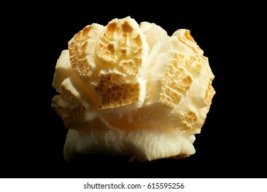 Single popped popcorn isolated on a black background with clipping path. Close-up or macro.