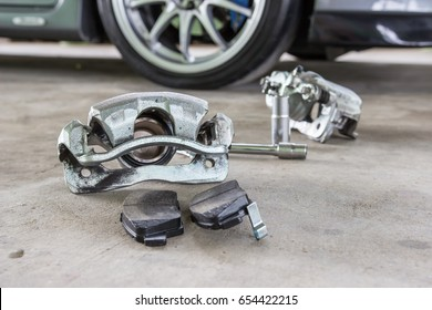 Single port caliper and brake pad on floor and car
