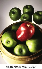 SIngle red apple with a basket of green apples
