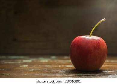 single red apple on wooden background