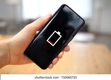 A single red bar in a battery icon on the touch screen of a mobile phone, held up by a male hand. A warning about the empty or low level of the battery power in the device. A charging concept.